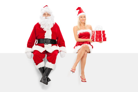 Man and woman in santa costume sitting on a panel isolated on white background photo