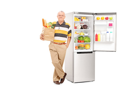 vertical fridge: Man holding bag with groceries by an open fridge isolated on white background