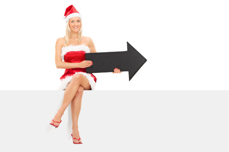 Girl in Santa costume holding an arrow seated on a panel isolated on white background