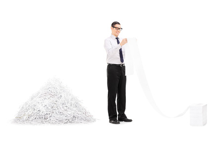 shredding: Man reading file in front of pile of shredded paper isolated on white background