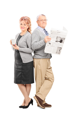 hot news: Full length portrait of a mature couple with a newspaper and cup of coffee isolated on white background Stock Photo