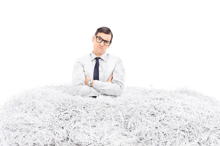 Displeased man standing in a pile of shredded paper isolated on white background