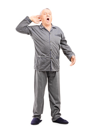 Full length portrait of a sleepy senior in pajamas stretching on white background Stock Photo