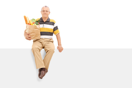 Senior holding bag with groceries seated on panel isolated on white background photo