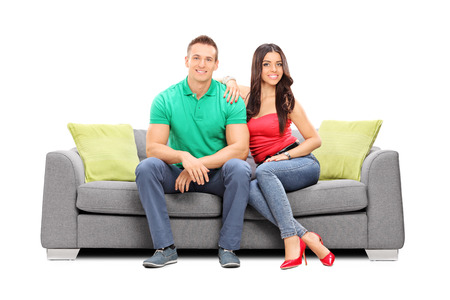 couple couch: Young couple posing seated on a modern sofa isolated on white background Stock Photo