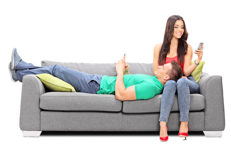 cell phone addiction: Couple relaxing with their cell phones on a sofa isolated on white background