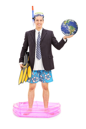Full length portrait of a businessman with diving mask holding the earth and standing in a small pool isolated on white background  photo
