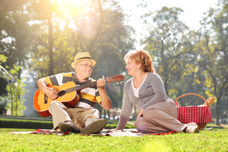playing music: Senior playing guitar for his wife on a picnic in park