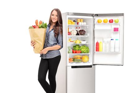 흰색 배경에 고립 된 오픈 냉장고에 의해 식료품 가방을 들고 여자 스톡 콘텐츠