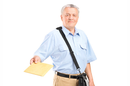 Mailman handing an envelope towards the camera isolated on white background Stock Photo