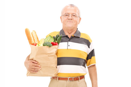 Senior walking with a bag of groceries isolated on white background photo