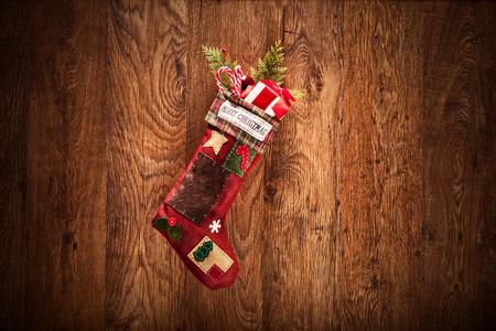 botas de navidad: Media de la Navidad que cuelga en una superficie de madera Foto de archivo