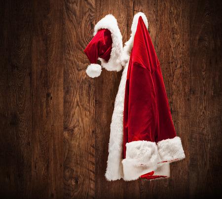 chaqueta: El traje de Santa que cuelga en un tiro de pared de madera con una inclinaci�n y una lente de cambio Foto de archivo