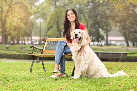 banc de parc: Jeune fille assise sur un banc dans un parc avec son chien Banque d'images