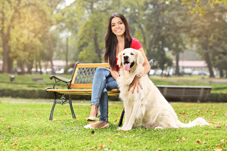 park bench: Young girl sitting on a bench in a park with her dog Stock Photo