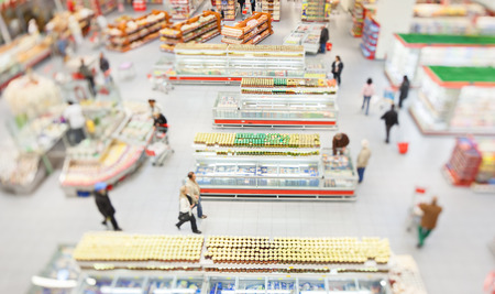 hall: People shopping in a large supermarket shot with a tilt and shift lens with the focus on the racks