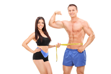 Woman measuring a handsome male athlete isolated on white background