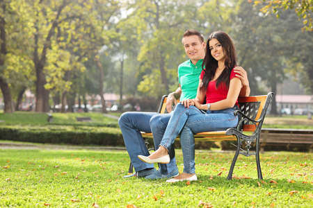 Young couple posing seated on a bench in park on a sunny day photo