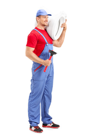 Full length portrait of a male plumber carrying a toilet and holding a plunger isolated on white background photo