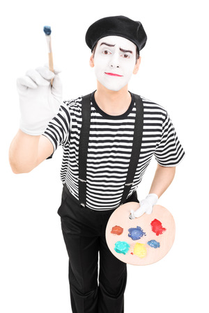 Male mime artist holding a paintbrush and a color pallet isolated on white background photo