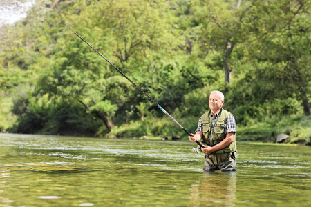 Mature fisherman fishing in a river on a sunny day Stock Photo