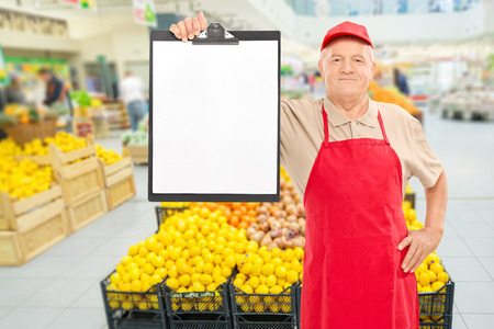 Mature market vendor holding a clipboard in front of an aisle with fruits and vegetables photo