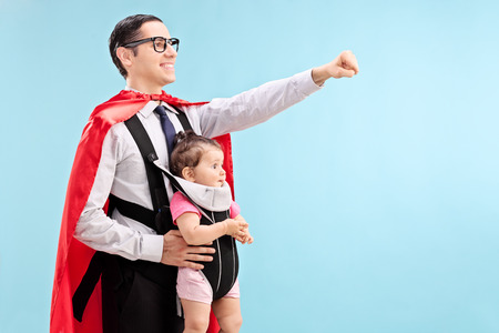 Proud father in superhero costume carrying his daughter with raised fist on blue background