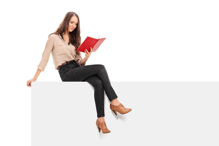 Young woman reading a book seated on a panel isolated on white background photo