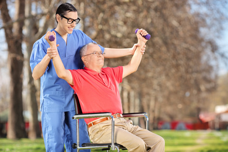 Physiotherapist exercising with a mature patient in park photo