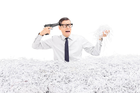shredding: Desperate man holding a gun to his head and standing in a pile of shredded paper isolated on white background