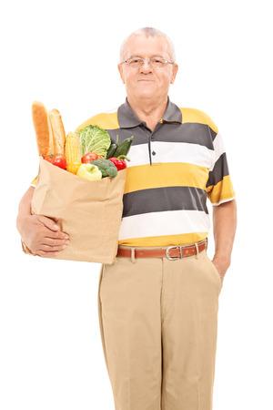 bolsa de pan: Hombre maduro que sostiene una bolsa llena de comestibles aisladas sobre fondo blanco