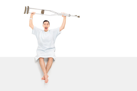 Overjoyed male patient raising his crutches in the air seated on a panel isolated on white background photo