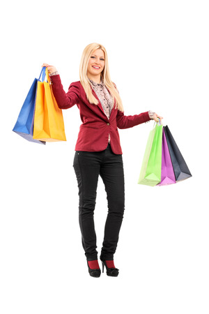 Full length portrait of an elegant woman holding shopping bags isolated on white background photo