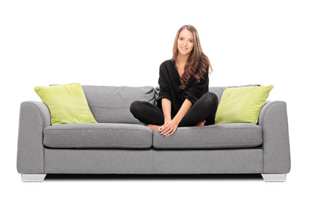 white sofa: Young woman sitting on a sofa and looking in the camera isolated on white background