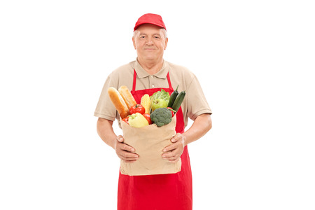 market vendor: Mature market vendor holding a grocery bag isolated on white background Stock Photo