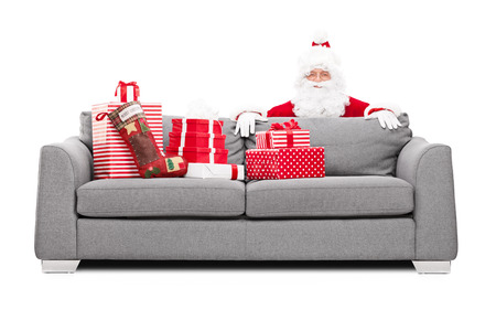 Santa Claus hiding behind a sofa full of Christmas presents isolated on white background