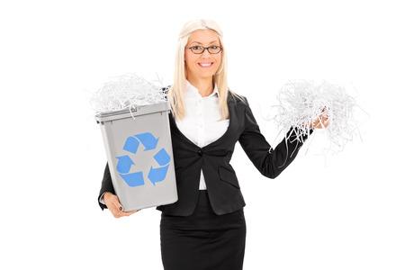 papelera de reciclaje: Negocios la celebraci�n de una papelera de reciclaje y el manojo de tiras de papel aislado en blanco
