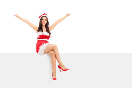 christmas costume: An overjoyed girl in Santa costume sitting on a panel isolated on white background Stock Photo
