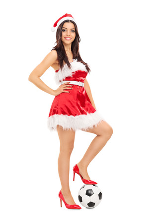 Girl in Santa costume with football under her foot isolated on white background photo