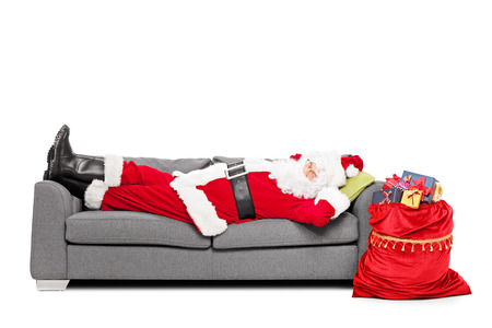 sofa: Santa sleeping on sofa with a bag of presents beside him isolated on white background