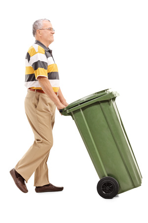 Full length portrait of a senior pushing a large green trash can isolated on white background Stock Photo