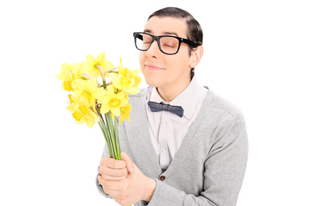 Young man smelling a bunch of yellow tulips isolated on white background