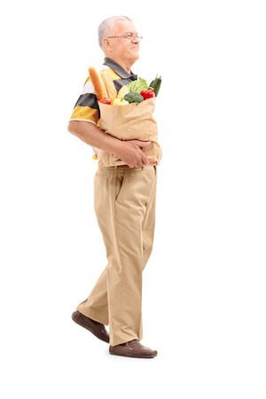 people walking white background: Full length portrait of a senior walking with a bag full of groceries isolated on white background