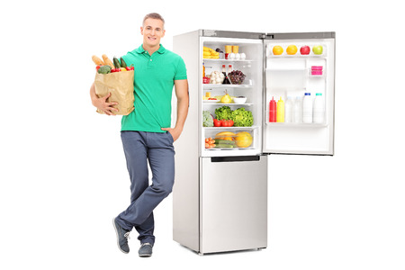 vertical fridge: Man holding grocery bag and standing by an open fridge isolated on white background