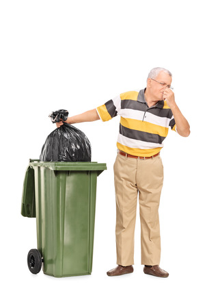 Full length portrait of a senior throwing away a stinky bag of trash isolated on white background photo