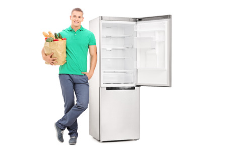 vertical fridge: Full length portrait of a man with grocery bag standing by an empty fridge isolated on white background Stock Photo
