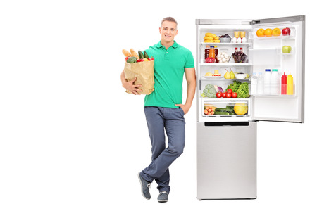 vertical fridge: Full length portrait of a young man standing by an open refrigerator and holding a grocery bag isolated on white background