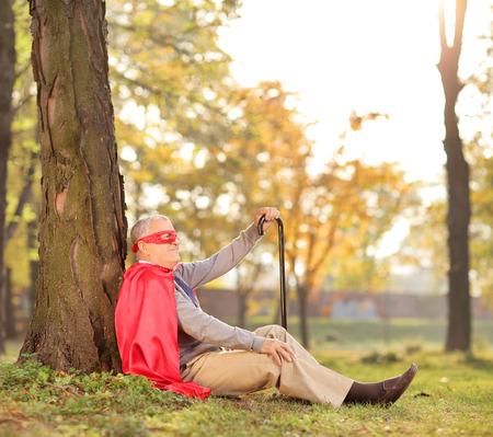senile: Senile old man sitting outdoors in a superhero costume shot with tilt and shift lens Stock Photo