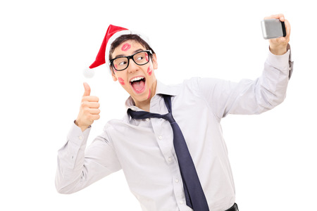 posing  agree: Guy covered in lipstick kisses giving a thumb up and taking a selfie isolated on white background