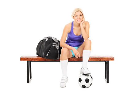 Female soccer player sitting on a bench isolated on white background photo